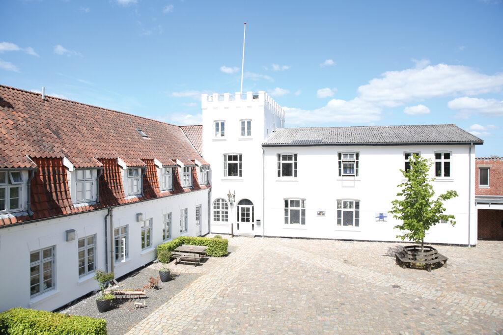 Gården på Uldum Højskole med hovedbygningen og tårnet.